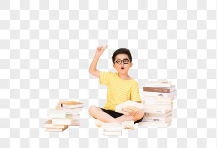 坐在书本旁的快乐小男孩图片