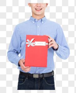 年轻男子手拿礼物盒特写图片