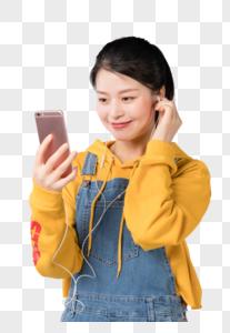 坐在椅子上看手机听音乐的学生图片