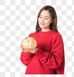 年轻女性手捧金猪储蓄罐图片