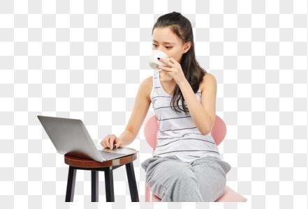 青年女性喝着咖啡使用电脑办公图片