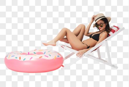 泳装美女坐在沙滩椅上与泳圈图片