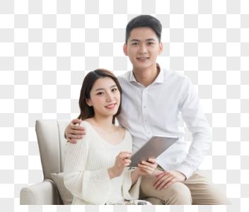 年轻夫妻幸福地坐在沙发上看平板电脑图片