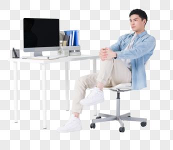 休闲商务男性办公桌前伸展筋骨图片