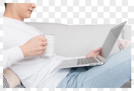 坐在沙发上打电脑的年轻男士图片