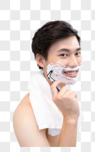 年轻男子在浴室剃须图片