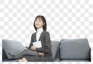 少女抱书坐在沙发上图片