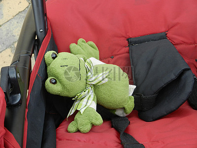 婴儿车上的绿色玩偶图片