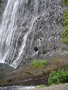 瀑布旁的人物留影图片