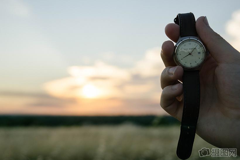 夕阳下手握着手表图片