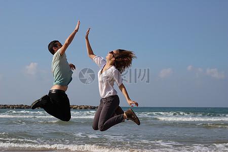 海边跳起击掌的男女图片
