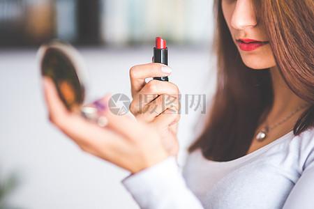 正在擦口红的年轻女子图片