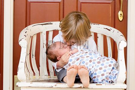 亲吻婴儿的金发小孩图片