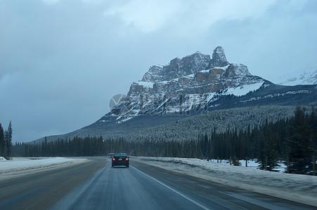 雪山下道路和行驶的车子图片
