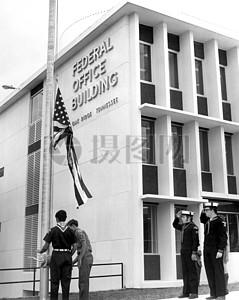在国旗下敬礼的男子图片