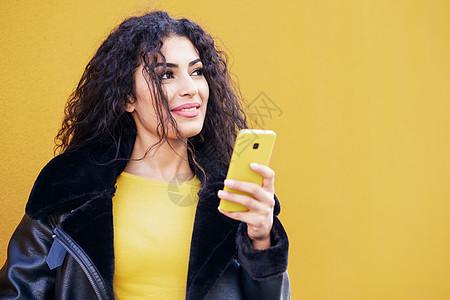 年轻的阿拉伯女人穿着休闲服,用她的智能手机黄色的城市墙上录制语音音符阿拉伯女人用她的智能手机走街上图片