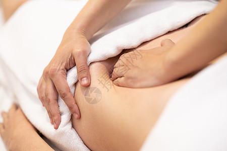 水疗沙龙接受腹部按摩的女人女性患者正接受专业骨病治疗师的治疗女性水疗沙龙接受腹部按摩图片