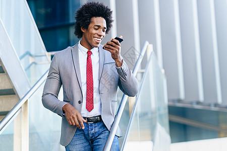 黑人商人办公楼附近用智能手机发送语音留言有AFRO头发的男人黑人商人办公楼附近用智能手机图片