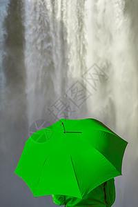 穿着绿色外套或夹克的年轻女子,瀑布前着把绿色的伞图片