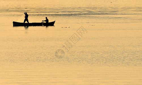 丹贝河上有橙色太阳的渔民的剪影图片