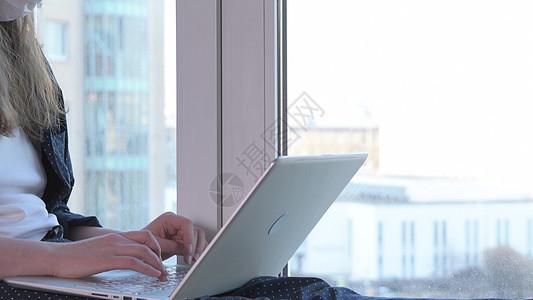 无聊的女人戴着面具看着窗户,家里工作,因为冠状病毒自隔离坐窗台上真正的家庭工作场所手持射击冠状病毒爆发妇图片