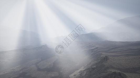 太阳的光线山脉的背景下,前景的熔岩岩石潮湿的海岸上阳光照射群山的背景上图片
