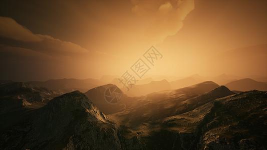 高山山峰上覆盖着戏剧性的浓雾雾蒙蒙的山夕阳的灯光下高山的山峰覆盖着戏剧性的浓雾图片