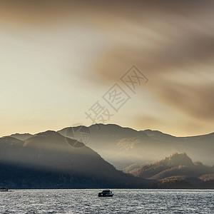 史诗般的日出景观,穿过湖区的德温特水,朦胧的太阳光束照亮了群山图片