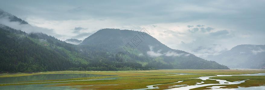平静的景色加大的山湖旁边,岩石平静的水中反射图片