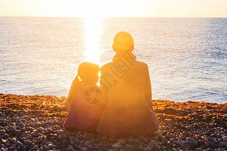 日落时海滩上的家人母女俩起跑步图片