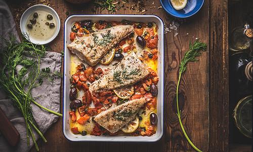 美味的鲈鱼鱼片地中海酱与西红柿,橄榄斗篷烤盘乡村木制背景与成分上面的风景图片