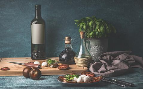 食物生活与油瓶,马苏里拉,西红柿厨房草药锅厨房的桌子背景图片