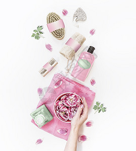 女手着水碗,白色桌面上有粉红色的花,有各种环保的水疗中心护肤工具化妆品瓶上面的风景现代天然化妆品零浪费图片