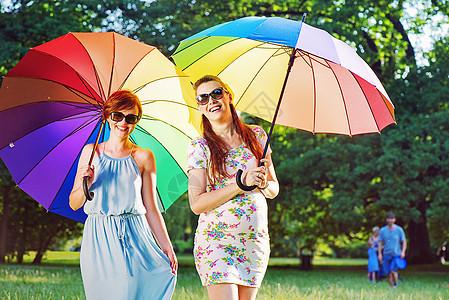 两位时尚的年轻女士摆着五颜六色的雨伞图片
