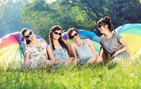 四个漂亮的女朋友着巨大的彩色雨伞图片
