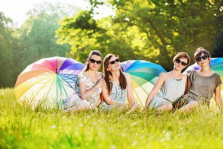 四位迷人的女士坐新鲜的草地上图片
