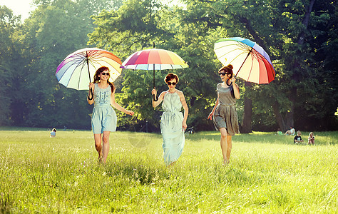 三个快乐的女人走夏日的草地上图片