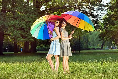 两位漂亮的女士着五颜六色的巨大雨伞图片