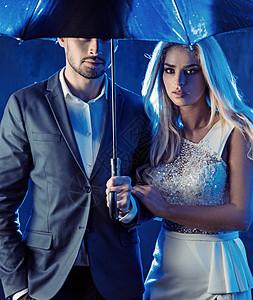 风情万种的年轻夫妇个下雨的酒吧里摆姿势图片