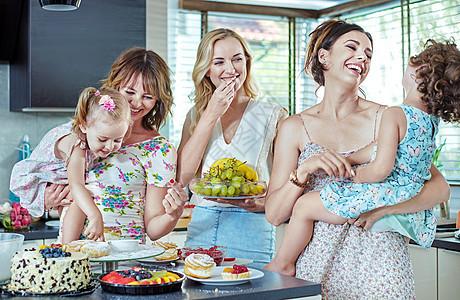 开朗的年轻女人他们的孩子起吃蛋糕糖果图片