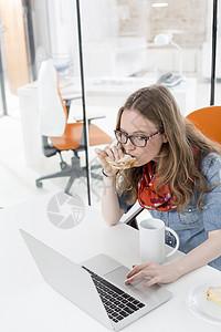 女商人办公室吃早餐时用笔记本电脑的触控板图片