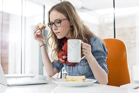 女商人办公室吃早餐时用笔记本电脑图片