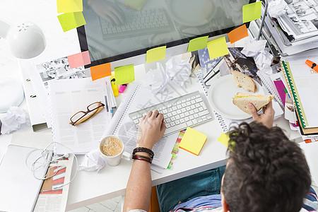 电脑上工作时,商人吃早餐的角度很高图片