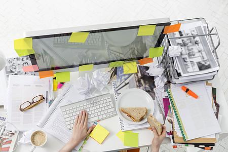电脑上工作的商人吃早餐的形象图片