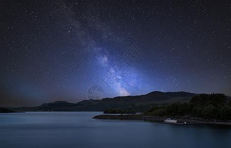 令人惊叹的充满活力的银河复合图像平静的湖泊景观与船岸上图片
