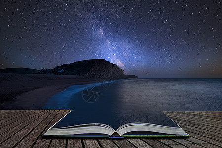 令人震惊的充满活力的银河复合图像,多塞特西湾长时间曝光的景观上,魔法故事书的页面中出来图片