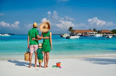 海滩上的家人,穿着绿色衣服的轻夫妇三岁的男孩马尔代夫的暑假图片