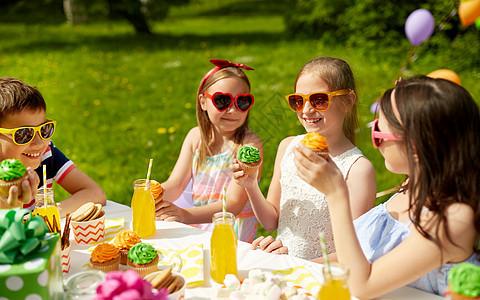 假期,童庆祝快乐的孩子戴着太阳镜坐桌子上的生日聚会夏季花园吃纸杯蛋糕孩子们夏天的生日聚会上吃纸杯蛋糕图片