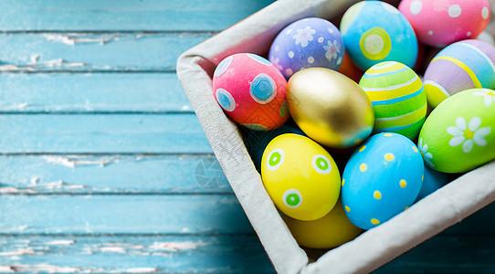 复活节,假日象彩色鸡蛋篮子蓝色老式木板背景篮子里彩色复活节彩蛋图片