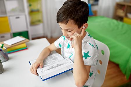 教育,童技术快乐的学生男孩耳机阅读书籍学外语家里学生男孩戴着耳机家看书图片
